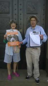 Eve Steadman (38 Degrees) with poster and Aidan Baker (Global Justice Cambridge) with petition, Cambridge Guildhall, anti-TTIP action, 22 August 2015.  Photo by Clare Baker