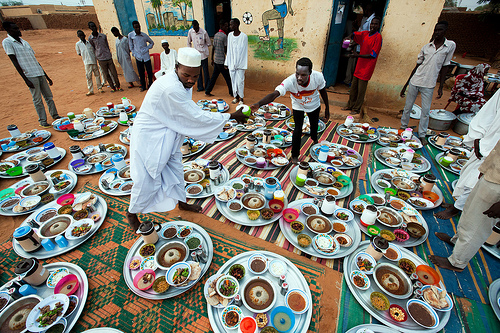 Two men set up trays with food in Al Tijane School in El Fasher for iftar, the evening meal that breaks the Muslim fast during the month of Ramadan.