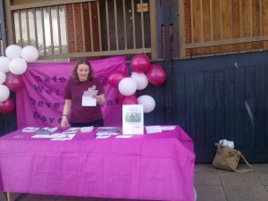 woman standing at stall with balloons in background